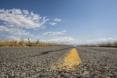 Yellow road center line, Salt Lake City. A painted yellow line in the center of an asphalt road under clouds near Salt Lake City , Utah Royalty Free Stock Photos