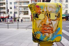 Painted yellow mailbox covered with street art by French graffiti muralist C215 in Paris Stock Photography
