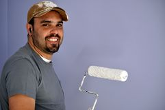 The painter. This picture represents a smiling Latin  painter holding the roller , wearing hat Royalty Free Stock Photos