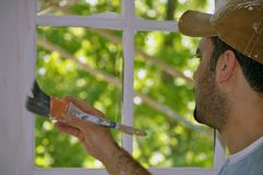 Painter. This picture represents a Latin painter on duty. He is holding a brush painting the window Royalty Free Stock Image