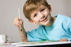 Painter. Isolated on white blond boy in blue t-shirt drawing the picture on the table Stock Photography