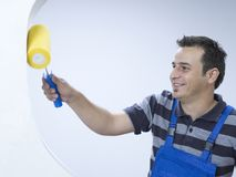 Painter. Young happy painter with paint roller Royalty Free Stock Image