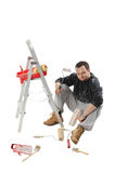Painter. Sitting and holding a paint rollers Royalty Free Stock Photo