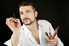 Painter in action. Creative artist in a white shirt on a black background with a brush Stock Image