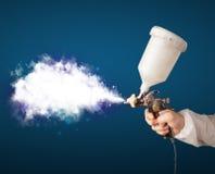 Painter with airbrush gun and white magical smoke Stock Photo