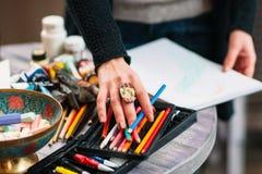 Painter artist chooses a color pencil. Closeup Royalty Free Stock Images