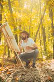 Painter artist forest. Art concept. Painting in nature. Start new picture. Painter with easel and canvas. Bearded man. Painter looking for inspiration autumn royalty free stock image