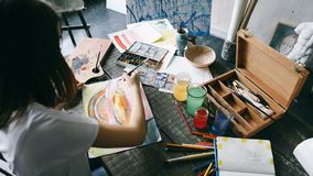PAinter artist girl is working. Work desk with paints and brushes. Inspiration mood stock video