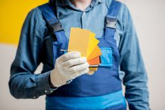 Painter with color swatches indoors. Painter in blue workwear holding color swatches on the yellow wall background indoors Royalty Free Stock Photos