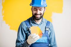 Painter with color swatches indoors. Painter in blue workwear holding color swatches on the yellow wall background indoors Royalty Free Stock Image