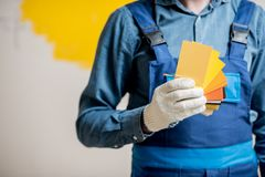 Painter with color swatches indoors. Painter in blue workwear holding color swatches on the yellow wall background indoors Royalty Free Stock Photo