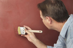 Painter Brushing Textured Red Wall Royalty Free Stock Images