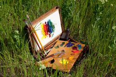 Painter case on grass with palette and artistic tools Royalty Free Stock Photos