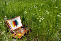 Painter case on grass with palette and artistic tools Royalty Free Stock Image