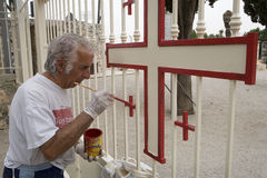 Painter Church Transfiguration. A worker uses red paint to highlight a Jerusalem Cross on a gate at the Church of the Transfiguration on Mount Tabor in Israel Royalty Free Stock Image
