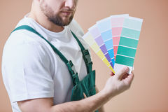 Painter with color palettes. Young house painter against brown wall with color palettes in his hand royalty free stock image