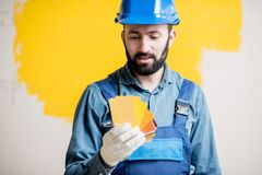 Painter with color swatches indoors. Painter in blue workwear holding color swatches on the yellow wall background indoors Royalty Free Stock Photography