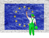 Painter covers brick wall with flag of European Union Royalty Free Stock Images