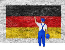 Painter covers brick wall with flag of Germany. Painter covers white brick wall with flag of Germany Royalty Free Stock Photography