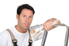 A painter and decorator. Leaning against a ladder and looking at us Royalty Free Stock Photo