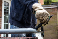 Painter decorator metalworker paints metal iron railing black with baggy jumper and workman's gloves Royalty Free Stock Photography
