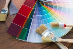 Painter and decorator work table with house project, color swatches, painting roller and paint brushes.  stock photos