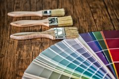 Painter and decorator work table with house project, color swatches, painting roller and paint brushes. High Dynamic Range tone stock photos