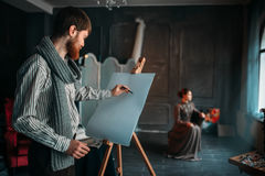 Painter drawing female portrait in art studio stock photography