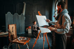 Painter drawing portrait against female poseur. Male painter drawing portrait against female poseur in studio. Oil paint Stock Image