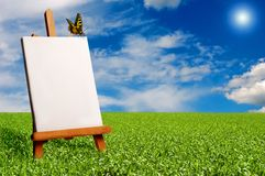 Painter easel outdoor. A blank painter easel in a meadow with a butterfly resting on it Royalty Free Stock Photo