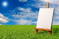 Painter easel outdoor. A blank painter easel in a meadow with a flock of birds flying in the sky Royalty Free Stock Photo