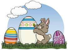 Painter Easter Bunny. The Easter bunny is busy painting his eggs for delivery. Bunny color and outline, eggs, grass and background on separate layers. Vector art Stock Photography