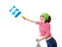 Painter female. Happy woman painting a wall an blue color, isolated on white. Worker female holding paint roller and renovating new home Stock Photography