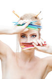 Painter girl. Young blond caucasian girl with brushes in hair holding color pencils while looking at camera Stock Images