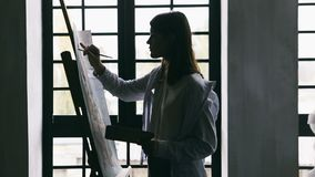Painter girl is drawinf in front of the window. White short. Creative mood moment. Video footage. Backlight stock footage