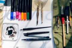 Painter, graphic designer or calligraphy work space, different kind of tools, brushes, marker and pen, place ready to create now d. Esign Stock Image