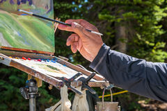 Painter Hand Brush and Easel. Hand of elderly male artist holding paintbrush and working on a landscape oil painting on a box easel with canvas and palette Stock Photo