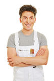 Painter with his arms crossed. Smiling painter with his arms crossed in a white overall Stock Photos