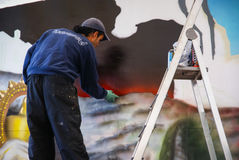 Painter and his painting on the wall at Covadonga, Spain stock photo