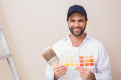 Painter holding a colour chart smiling at camera Royalty Free Stock Photos