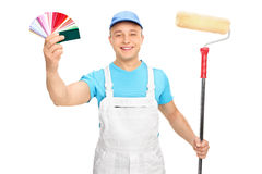 Painter holding a paint roller and color guide Royalty Free Stock Image