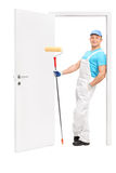 Painter holding a paint roller and leaning on a door. Full length portrait of a young painter holding a paint roller and leaning on the frame of an opened door Stock Photos