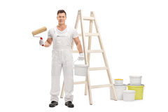 Painter holding roller and color bucket in front of ladder Stock Photo
