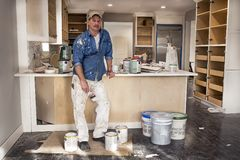 Painter holding wet paint brush standing in messy remodeled home kitchen surrounded by paint cans. Painter wearing painters clothes holding paint brush and Royalty Free Stock Photos