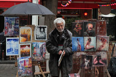 A painter among its pictures on Place du Tertre, in Paris Royalty Free Stock Photo