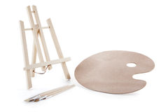 A painter kit, easel and palette  on the background. Royalty Free Stock Photography