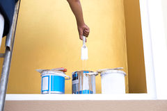 Painter on a ladder dipping his brush into the paint can Stock Photography