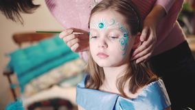 Painter makes butterfly shape at girl`s face. Painter hand draws face painting to little girl. Aqua makeup. Child with funny face painting. Medium close up stock footage
