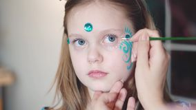 Painter makes butterfly shape at girl`s face. Painter hand draws face painting to little girl. Aqua makeup. Child with funny face painting. Medium close up stock video footage