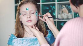 Painter makes butterfly shape at girl`s face. Painter hand draws face painting to little girl. Aqua makeup. Child with funny face painting. Medium close up stock video